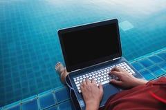 使用计算机膝上型计算机的一个人,在有浸洗的腿游泳池边在水中 裁减路线屏幕 免版税库存图片