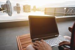 使用计算机膝上型计算机的一个人,晒日光浴躺椅在游泳池在城市,选择聚焦 裁减路线屏幕 免版税库存照片
