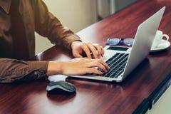 使用计算机膝上型计算机的商人手在有sunli的办公室 库存图片