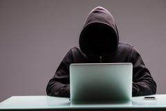 使用计算机膝上型计算机的未知的黑客程序员为文丐通知 图库摄影