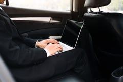 使用计算机运转的汽车的商人里面 库存照片