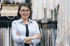 使用计算机,两名妇女与帷幕的,室内装饰品,女性织品一起使用选择织品 工作场所设计师,卖主  库存照片