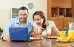 使用设备的愉快的夫妇在早餐期间 免版税库存图片