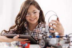 使用设备的有天赋的青少年的女孩在科学演播室 免版税库存照片
