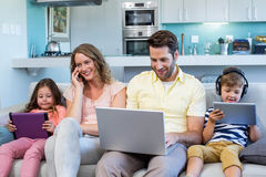 使用设备,在长沙发的愉快的家庭一起 库存图片