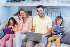 使用设备,在长沙发的愉快的家庭一起 免版税库存图片