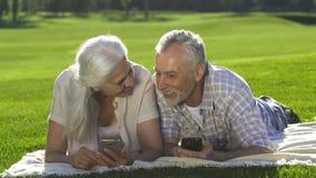 使用说谎在草坪的手机的资深夫妇 影视素材