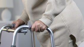 使用走的框架的微弱的年长妇女在脊髓手术以后在康复中心 股票视频