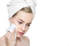 使用软的面孔抹,有在毛巾包裹的她的头发的可爱的年轻白肤金发的妇女,去除组成 库存照片