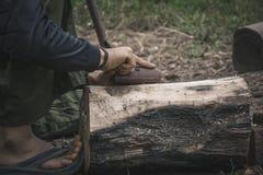 使用辐刀的木匠的手装饰木制品的树干 免版税库存照片