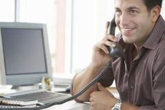 使用输送路线电话的愉快的商人在办公室 库存照片