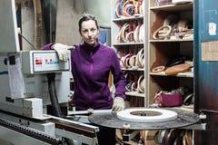 使用边缘机器的女工做家具在木匠 免版税库存图片