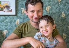 使用近在房子里的微笑的愉快的爸爸和儿子 愉快的系列 库存图片