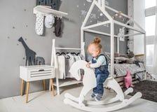 使用近在有玩具马的, ska屋子里的一岁的女孩 免版税库存照片