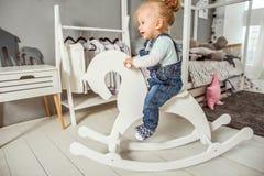 使用近在有玩具马的, ska屋子里的一岁的女孩 免版税图库摄影