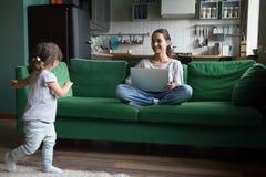 使用逗人喜爱的活跃的女孩,当在家时使用膝上型计算机的母亲 免版税库存图片