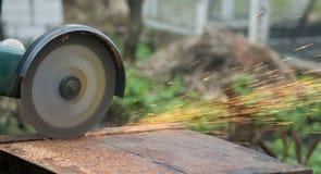 使用通报的人为处理金属constructionman看见了使用处理的金属建筑一把圆锯 免版税库存照片