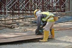 使用通报的木匠在建造场所看见了 库存图片