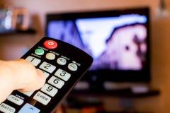 使用遥控改变在电视的channesl 免版税库存照片