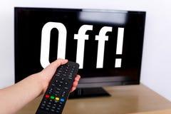 使用遥控的手关闭电视与文本 免版税库存照片