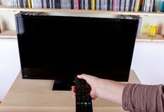 使用遥控的手关闭电视 免版税库存照片