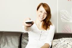 使用遥控的年轻愉快的妇女 图库摄影