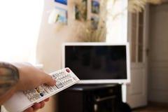 使用遥控,人` s手交换在电视的渠道 免版税库存图片