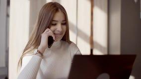 使用遥远的工作的,一台膝上型计算机一个年轻自由职业者女孩在咖啡馆坐 股票视频