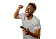 使用遥远的控制器的美国黑人的人打激动的电子游戏愉快和 免版税库存照片