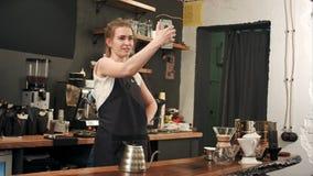 使用采取的智能手机的快乐的女性barista在咖啡店的selfie 免版税库存图片