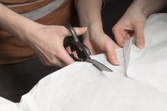 使用金属剪刀,妇女切开纸片 免版税库存照片
