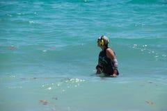 使用金属探测器的妇女在海洋 免版税库存照片