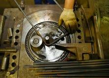 使用钢立弯机弯机钢筋的专家为修造 免版税库存图片