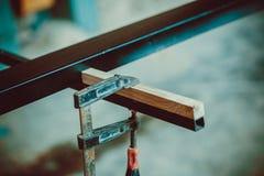 使用钳位的工匠固定两块木头和铁 免版税库存照片
