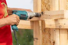 使用钻子藏品在木杆建筑或专栏模板的板条板关闭工作员播种的照片  免版税库存图片