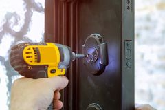 使用钻子螺丝刀,安装与锁,木匠的门把手螺丝,特写镜头 免版税库存照片