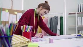 使用铅笔的年轻亚洲妇女时装设计师图画和看纸,当工作在车间演播室时 影视素材