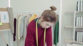 使用铅笔的年轻亚洲妇女时装设计师图画和看纸,当工作在车间演播室时 股票录像