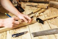 使用铅笔的木匠采取在木头的测量 免版税库存照片