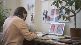 使用铅笔,女性时装设计师是画,坐在桌上在缝合的车间,妇女完成创造性的工作 股票录像
