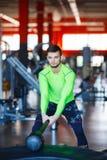 使用锤子和轮胎,一个年轻人在健身房训练 免版税库存图片