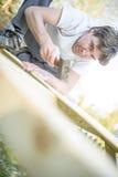 使用锤子或短槌的低角度观点的年轻人钉牢n 免版税库存图片