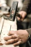 使用锤子的木匠为他的工作在木匠业车间 图库摄影