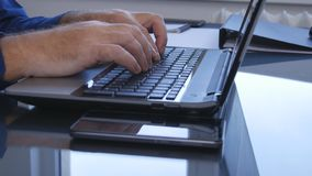 使用键盘,有一台膝上型计算机的买卖人在内部办公室输入数据 库存图片