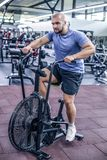 使用锻炼脚踏车的年轻人在健身房 使用空气自行车的健身男性为心脏锻炼在crossfit健身房 图库摄影