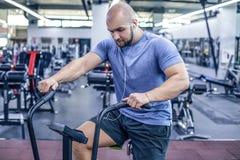 使用锻炼脚踏车的年轻运动员在健身房 使用空气自行车的健身男性为心脏锻炼在crossfit健身房和listenin音乐 免版税库存图片