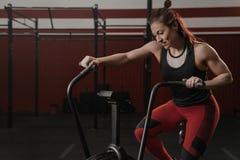 使用锻炼脚踏车的Crossfit妇女在健身房 库存照片