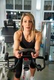 使用锻炼脚踏车,白肤金发的运动的妇女在健身房行使 库存图片