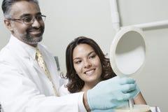 使用镜子的牙医和患者 图库摄影