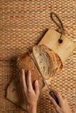 使用长的刀子切口面包的女性手在显示空气面粉纹理的木刻 库存图片